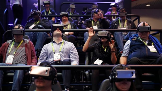 People look through Samsung Gear VR virtual reality goggles at the Samsung booth during the CES show, Tuesday in Las Vegas.