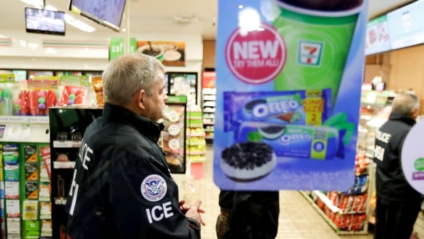 U.S. Immigration and Customs Enforcement agents serve an employment audit notice at a 7-Eleven convenience store on Wednesday in Los Angeles.