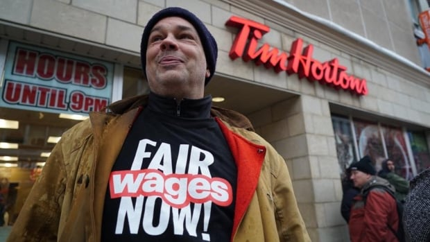 Labour activist Anthony Veberchmoes stood alongside 40 others outside of Tim Hortons in downtown London, protesting the negative fallout of minimum wage increases.