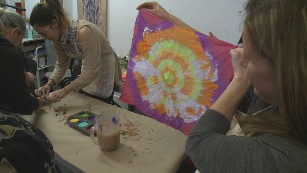 Danah Beaulieu, owner of Art InDeed Studio, holds up art created at Alzheimer Society program.