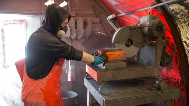 A worker cuts a core sample as part of work for the Courageous Lake gold project. Seabridge Gold is resuming winter drilling there after a hiatus of several years.