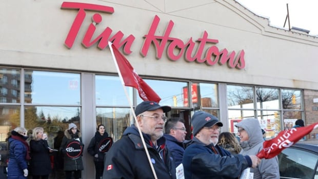Protestors gathered earlier this week outside Tim Hortons locations following the decision by some franchises to cut employee benefits in response to Ontario's new minimum wage law.