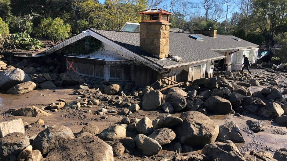 A damaged house surrounded by large boulders and debris following mudslides due to heavy rains in Montecito, Calif.