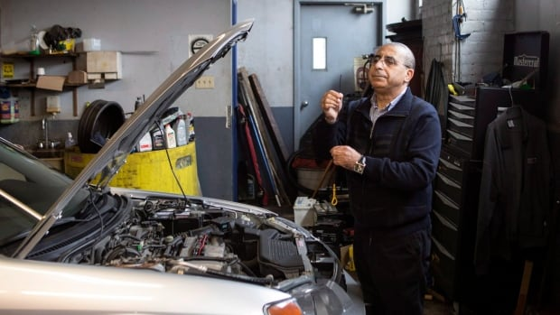Mohamed Bouchama, consultant for Car Help Canada, checks the oil level as he inspects a used car at a mechanic's garage in Toronto on January 10, 2018.