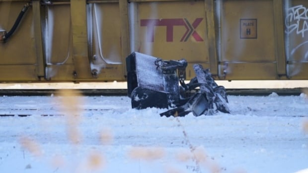 A police car sits at the scene of a fatal crash in downtown London on Tuesday between a CN freight train and a sidewalk snowplow.