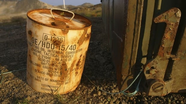 A rusty container of lubricant oil for a U.S. military vehicle stands among abandoned U.S. military material on Aug. 16, 2005, outside the eastern Greenland settlement of Kulusuk where there used to be an U.S. Air Force base as part of an early warning radar system.