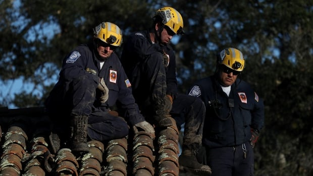 An Orange County urban search and rescue team takes a break on the roof a house in Montecito.