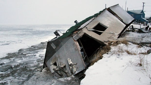 An abandoned house at the west end of Shishmaref, Alaska, sits on the beach after sliding off during a fall storm in 2005. State health officials are warning that serious health issues could crop up as the state warms. Warming already has thawed soil and eroded coastlines, leading at least three villages, Shishmaref, Kivalina and Newtok to consider relocating.