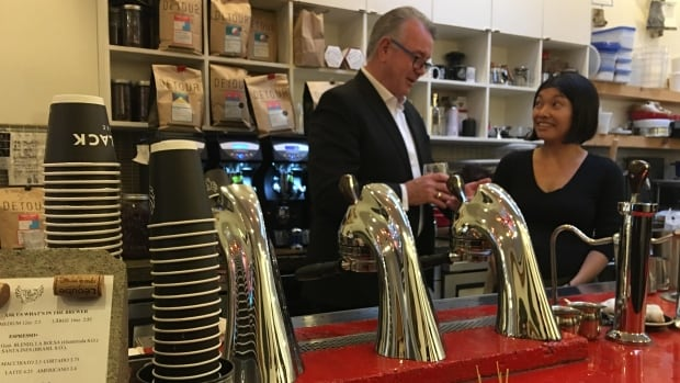 Ontario Labour Minister Kevin Flynn meets Nozomi Morimoto, a barista at HotBlack Coffee on Queen Street West in Toronto. She just received her first paycheque since the minimum wage went up.