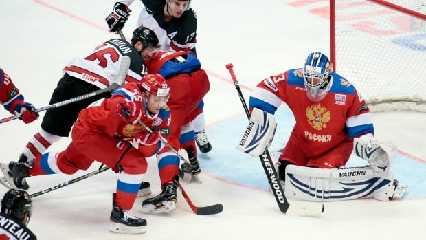 Canada's Rene Bourque, top, and Brandon Kozun try to score against Russian goalie Vasili Koshechkin during the Channel One Cup match in Moscow on Dec. 16, 2017.