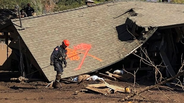 Firefighters search homes damaged by deadly rain and mudflow in Montecito, Calif., on Friday. Dozens of homes were swept away or heavily damaged and several people were killed Tuesday as downpours sent mud and boulders roaring down hills stripped of vegetation by the gigantic Thomas wildfire in Southern California last month.