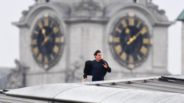 Actor Tom Cruise runs along the rooftop of Blackfriars station during filming for the new Mission Impossible 6 film in London Saturday.