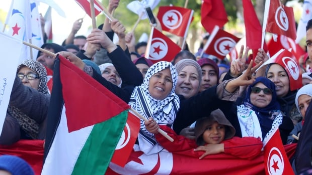People wave national flags during demonstrations on the seventh anniversary of the toppling of president Zine el-Abidine Ben Ali, in Tunis.