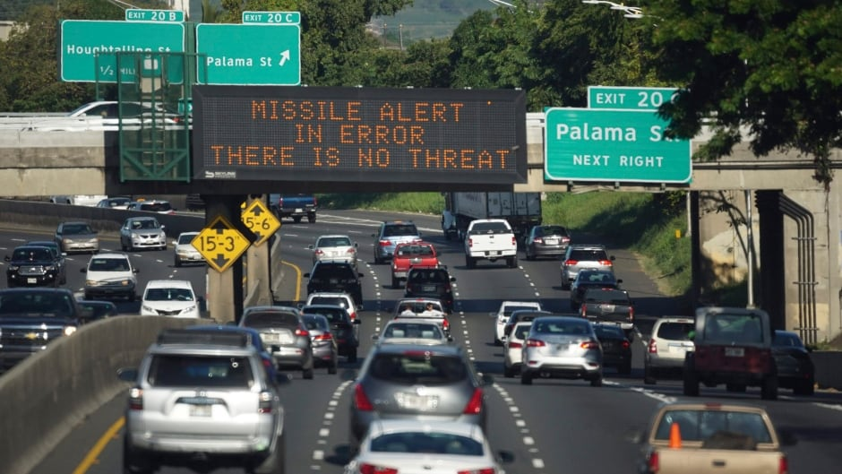Cars drive past a highway sign cancelling a missile alert on the H-1 Freeway in Honolulu.