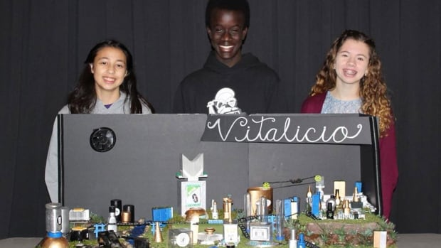 Christianne Riveroll, Christian Ndayegamiye, and Penelope Able pose with part of their display for this year's Future City Competition in Washington, D.C.