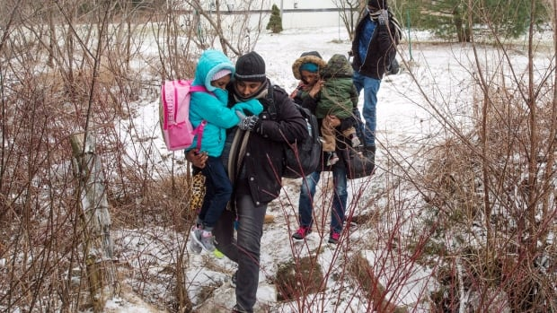 A group of refugee claimants are seen crossing into Canada last year. The Salvation Army and PRAIDA say warm winter clothes are needed for newcomers who don't have the proper attire to protect themselves from this winter's harsh temperatures.