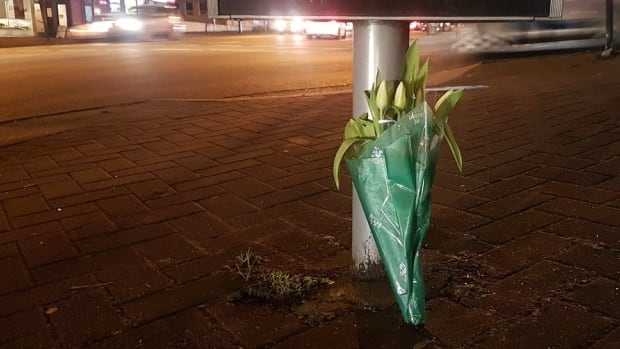 Flowers mark the intersection were Alfred Wong, 15, was shot while riding in a vehicle with his parents near East Broadway and Ontario Streets, a busy intersection south of Vancouver's downtown, on Saturday.