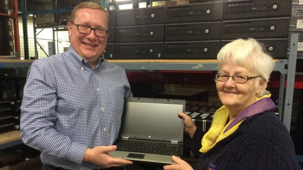 John Brennan of Computers for Success shows Doreen Wall one of the laptops that will be delivered soon to a member of the P.E.I. Women's Institute.
