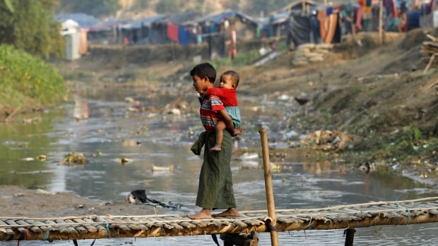 A Rohingya refugee child, carrying another child, walks along a bridge from Myanmar's border to Bangladesh on Friday. A government plan calls for Rohingya refugees in Bangladesh to start returning to Myanmar next week.