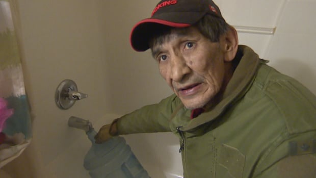 Gary Grandbois fills a jug with water from the bathtub of his sister's trailer. He has no running water in the shack where he lives.