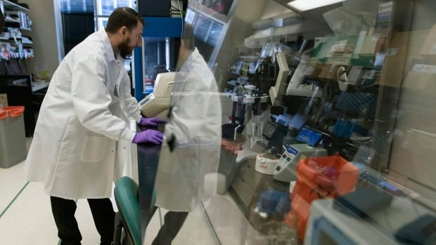 Biologist Jason Plyler prepares to test how immune cells react to possible flu vaccines at the Vaccine Research Center at the National Institutes of Health, Tuesday, Dec. 19, 2017, in Bethesda, Md.  As scientists mark the 100th anniversary of the 'Spanish' influenza pandemic, labs are hunting better vaccines.