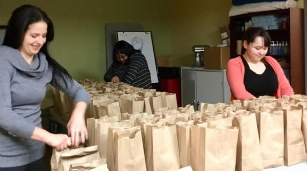 Volunteers fill brown-bag lunches in Nain