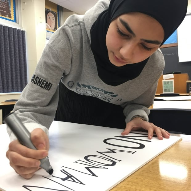 students work on signs for the women's march
