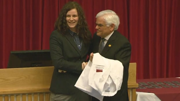 Julia Collins accepts an honorary white coat from Don Rowe on behalf of her father, David, who was killed in December of 2016.