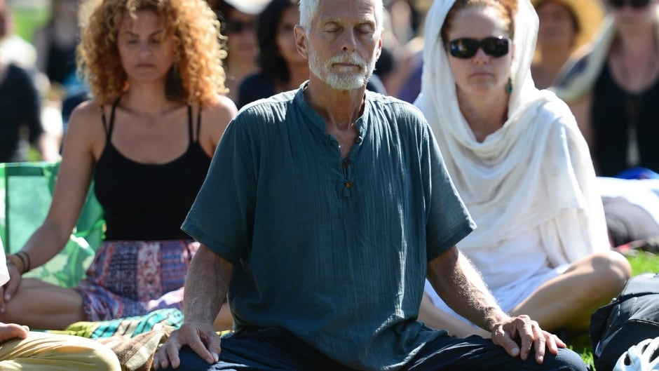 People take part in a mass meditation on the lawn of Parliament Hill in Ottawa on Thursday, Sept. 21, 2017. THE CANADIAN PRESS/Sean Kilpatrick
