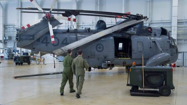Two airmen walk toward a CH-124 Sea King helicopter at 12 Wing Shearwater on Friday.