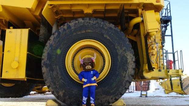 The Alberta Winter Games mascot poses with a piece of heavy equipment in Fort McMurray, Alta.
