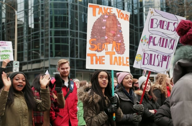 Marchers wave placards at the 2018 Women's March in Ottawa