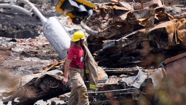 A firefighter walks by rubble on the train crash site in Lac-Mégantic, Que., July 14, 2013.