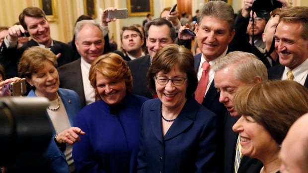U.S. Senators Susan Collins, centre right, addresses reporters with fellow Senators' Jeanne Shaheen, Tim Kaine, Heidi Heitkamp, Joe Manchin, Lindsey Graham, Amy Klobuchar and Jeff Flake after lawmakers struck a deal to reopen the federal government three days into a shutdown on Capitol Hill in Washington on Monday.