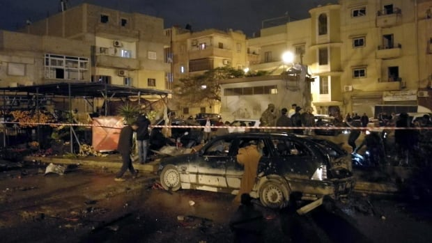 People gather in the aftermath of twin car bombs late Tuesday in Benghazi, Libya.