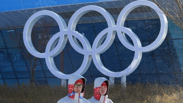 Volunteers stand in front of the Olympic rings at the Main Press Centre for the 2018 Winter Olympics in Pyeongchang, South Korea. Domestic interest in the Games has been muted.