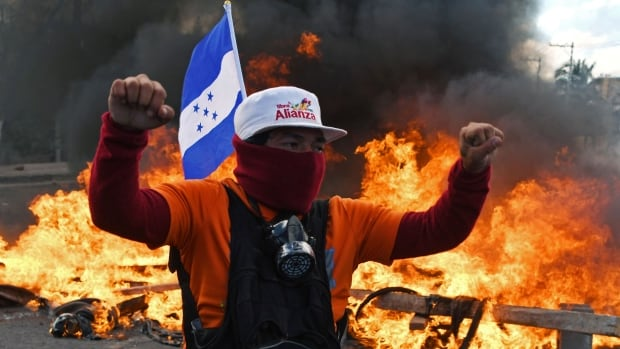 A Honduran Opposition Alliance Against the Dictatorship supporter protests against president Juan Orlando Hernandez's re-election, while the inauguration ceremony takes place at the Tiburcio Carias Andino national stadium, in Tegucigalpa, on Saturday.