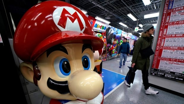 A Super Mario figure greets shoppers at a Tokyo shop on Wednesday. Nintendo said a Super Mario film is in the works, as part of a larger announcement that its profit jumped 31 per cent in April-December from a year earlier, aided by the popularity of its Switch hybrid console.