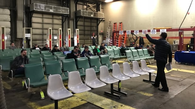 A handful of bidders wait for their chosen lot to be called in the old STC warehouse in Saskatoon.