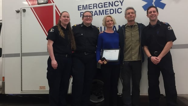 Luanne Katz, centre, holds her B.C. Emergency Health Services Vital Link certificate and award for performing life-saving CPR on her husband Ken Katz, second from right. She was joined at the award ceremony by paramedics and the dispatcher, Rachel Wardale, far left, who took her 911 call.