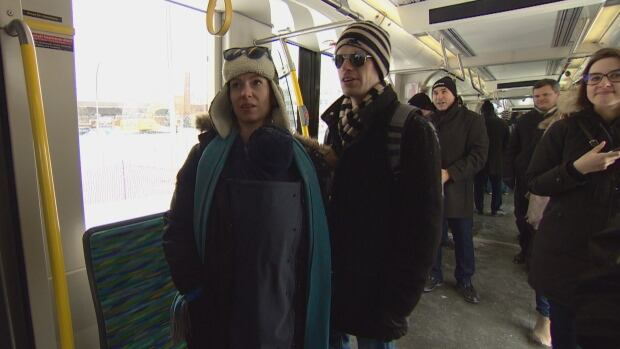 People stand in a mock-up of one of the new LRT cars that will be used on the Valley Line.