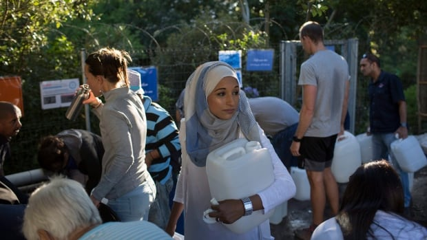 A woman waits to collect water at a source for natural spring water in Cape Town on Thursday, Feb. 1 as the drought-hit city of Cape Town introduced new water restrictions.