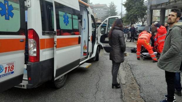 Paramedics help one of the wounded who was shot from a passing vehicle in Macerata, Italy.