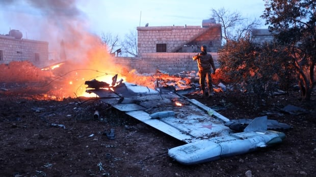 A picture taken Saturday shows a rebel fighter taking a picture of what has been identified as a downed Su-25 fighter jet, near the Syrian city of Sarqeb, southwest of Aleppo.