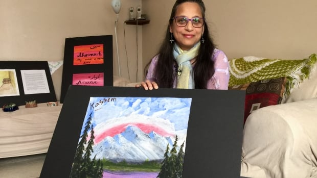 Amrita Deshpande shows off the artwork of one participant, depicting Waterton Lakes National Park.
