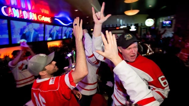 Fans celebrate at a Vancouver sports bar in Feb. 2014, after the Canadian Olympic men's hockey team defeated the U.S. 1-0 in the semifinal at the Sochi Winter Olympics. The time difference between 2018 Olympics host Pyeongchang and many Canadian cities will mean the puck drops for some hockey games as early as 2:40 a.m. ET.