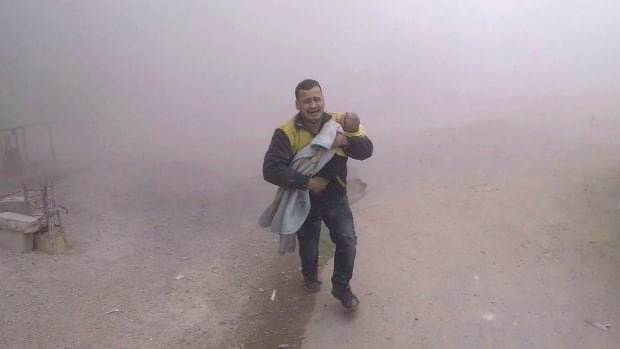 This photo provided by the Syrian Civil Defense group known as the White Helmets shows what it says is one of its paramedics carrying his wounded son after airstrikes hit a rebel-held suburb near Damascus on Tuesday.