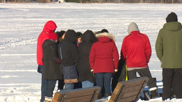 A crowd gathers at Gillies Lake Tuesday afternoon following reports of the death of 21-year-old Joey Knapaysweet and 62-year-old Agnes Sutherland.