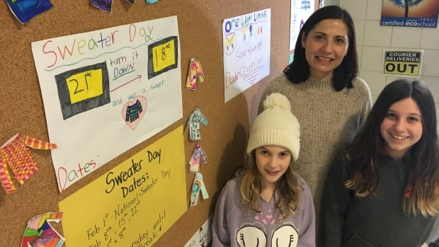 Grade 5 teacher Lisa Hamelin and her students Kennedy Taylor, right, and Niamh Priest, left, are taking part in Sweater Day, where students dress warmly so the school can lower the temperature and cut energy costs.
