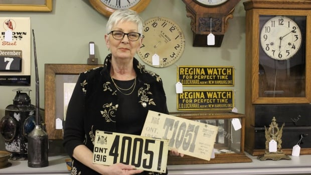 Bonnie Berndt holds up license plates that her grandfather, Emerson Luckhardt, collected during the time of World War I. Each is valued at approximately $1,500.